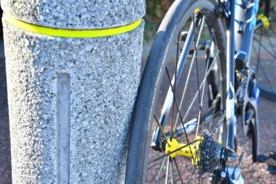 後輪タイヤのサイドグリップ面を電柱やポールに接触させて固定させる